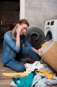 emocionální hospodyně při pohledu na oblečení před uvedením do pračky v domácnosti