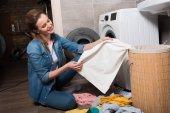 Hausfrau nimmt Kleidung, um sie zu Hause in die Waschmaschine zu legen