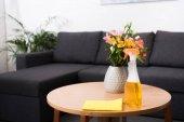 zblízka pohled květin v váza, pracího prostředku a hadr na dřevěný konferenční stolek