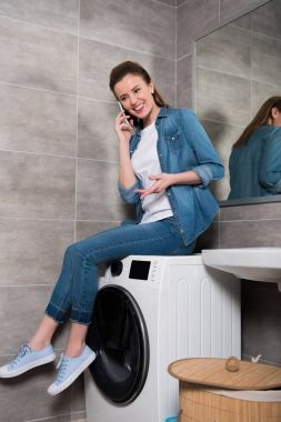 cheerful housewife talking on smartphone while sitting on washing machine at home
