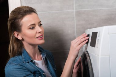 side view of attractive housewife operating washing machine at home