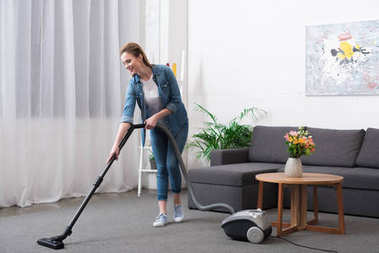 attractive woman with vacuum cleaner cleaning room at home