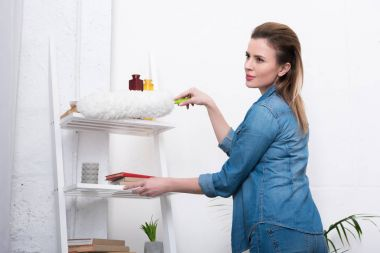 side view of woman in casual clothing with dust cleaning brush cleaning home