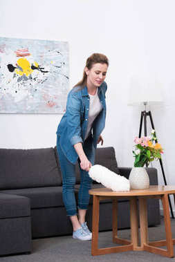 woman in casual clothing with dust cleaning brush cleaning home
