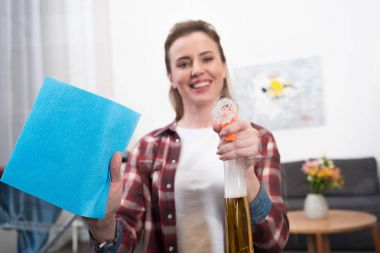 selective focus of smiling woman with detergent and rag cleaning home