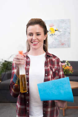 portrait of smiling woman with detergent and rag cleaning home