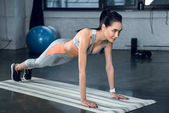 Photo young athletic woman doing plank on yoga mat at gym