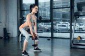 mladá sportovní žena dělá dřepy s deskovými závažími v tělocvičně