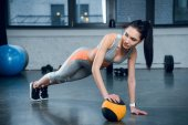 mladá sportovní žena dělá push up s jednou rukou na kouli v tělocvičně