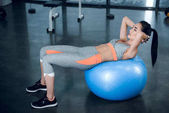 young sporty woman lying on firball at gym