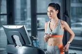 Fotografie junge athletische Sportlerin mit Smartphone auf Laufband im Fitnessstudio