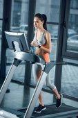 junge attraktive Sportlerin joggt im Fitnessstudio auf dem Laufband