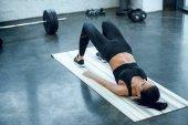 mladá sportovní žena dělá most cvičení v tělocvičně