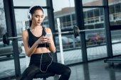 Fotografie junge, fitte Frau entspannt sich im Fitnessstudio und hört Musik mit Kopfhörern