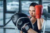 Fényképek női ökölvívó edző edzőteremben gyakorlása