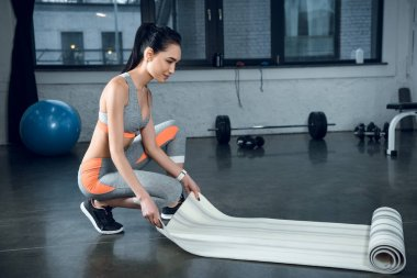 young athletic woman rolling yoga mat after exercises at gym