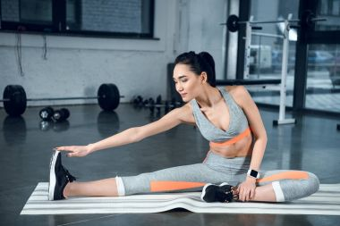 young athletic woman doing side bend on yoga mat at gym