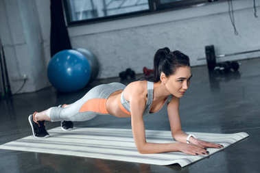 young fit woman doing plank on yoga mat at gym