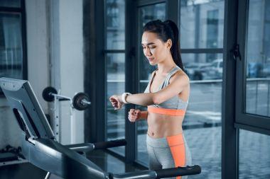 young athletic sportswoman checking fitness tracker while running on treadmill at gym