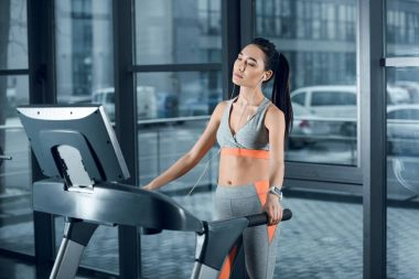 young athletic sportswoman jogging on treadmill and listening music with earphones at gym