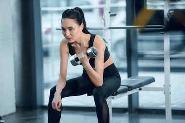 young sporty woman exercising with dumbbell while sitting on workout bench at gym