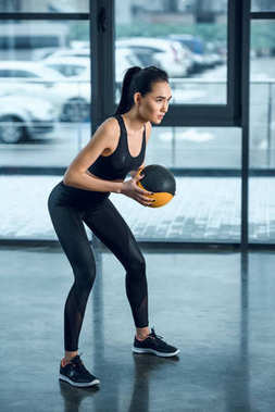 young athletic woman exercising with ball at gym