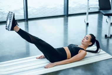 young sporty woman doing V-ups on yoga mat at gym