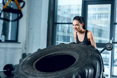 young strong woman flipping workout wheel at gym