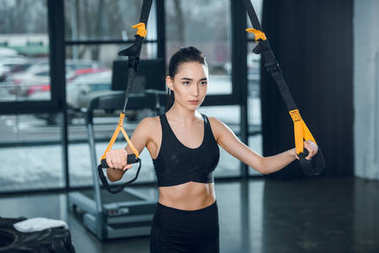 young fit woman working out with resistance bands at gym
