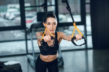 attractive fit woman working out with suspension straps at gym