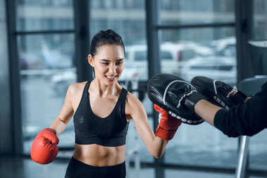 sporty young female boxer exercising with trainer at gym