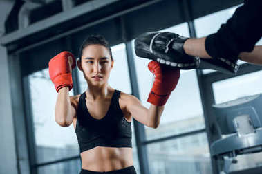 young female boxer exercising with trainer at gym