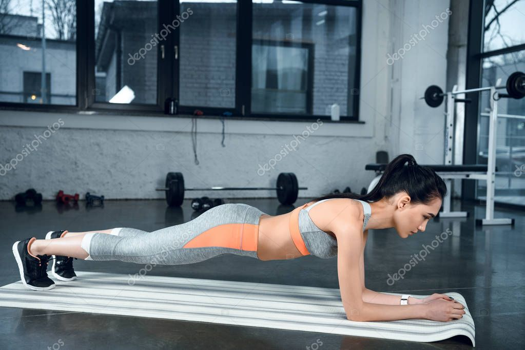 young sporty woman doing plank on yoga mat at gym