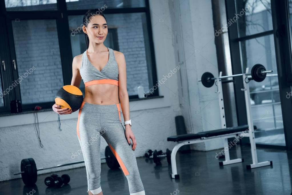 young sporty woman standing with mini pilates ball at gym
