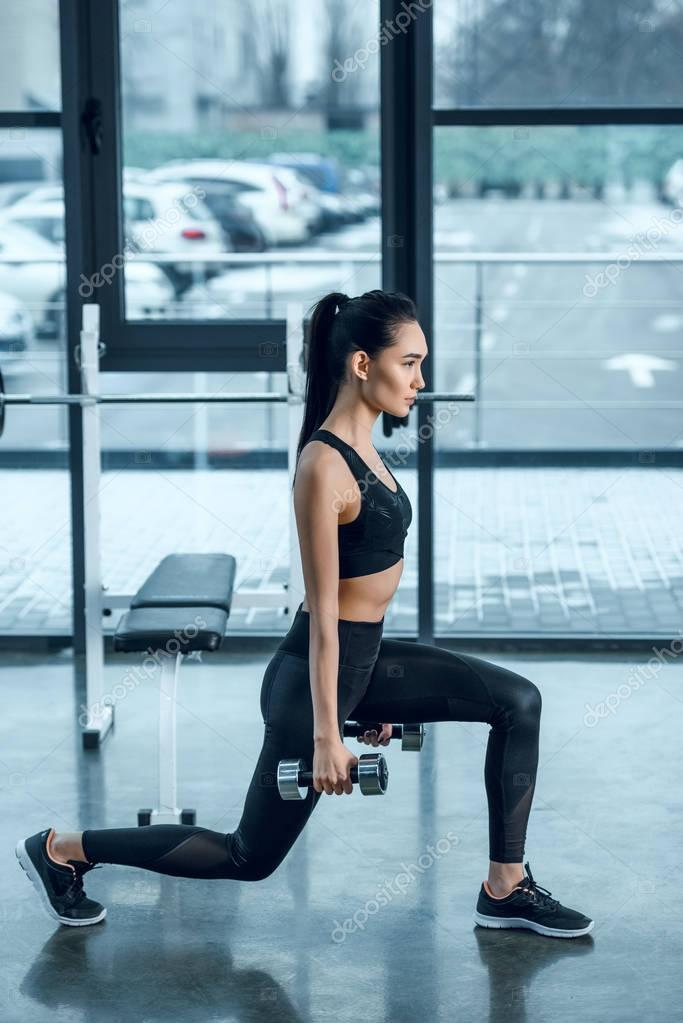 side view of young fit woman doing single leg squats with dumbbells at gym