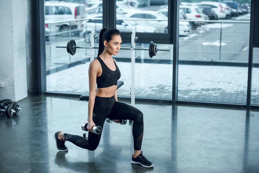 young sporty woman doing single leg squats with dumbbells at gym