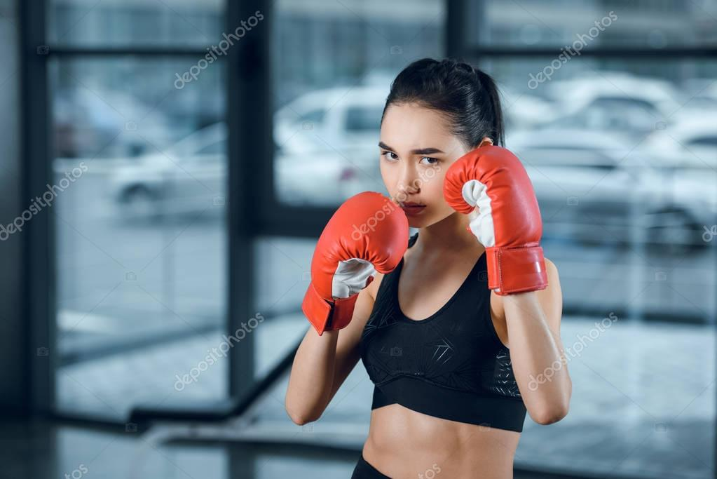 young female boxer in gloves at gym looking at camera