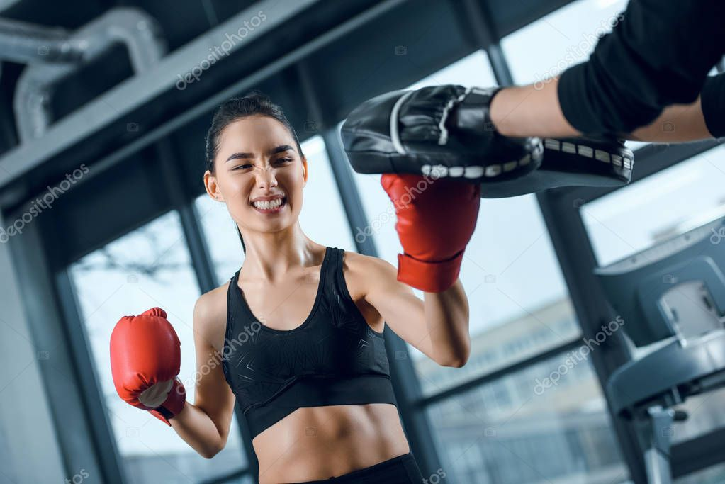 expressive young female boxer exercising with trainer at gym