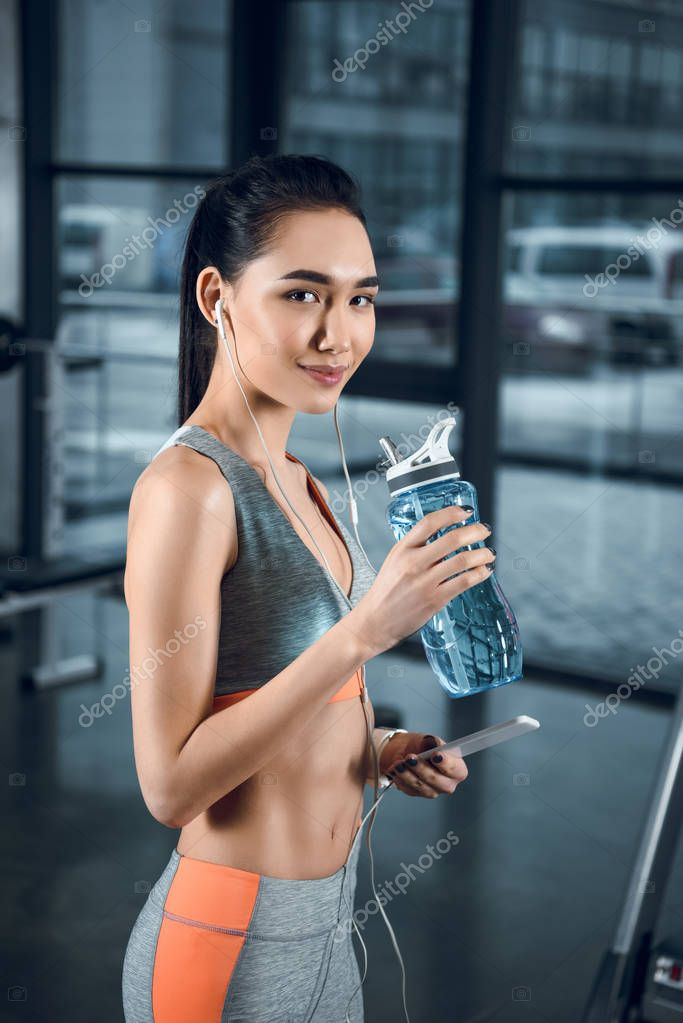 young fit woman with bottle of water at gym
