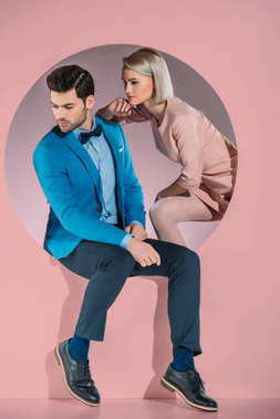 beautiful couple in stylish clothes looking down on pink