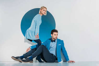 attractive stylish couple sitting and looking at camera on grey