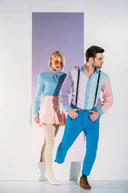 attractive couple in fashionable clothes going through frame on white