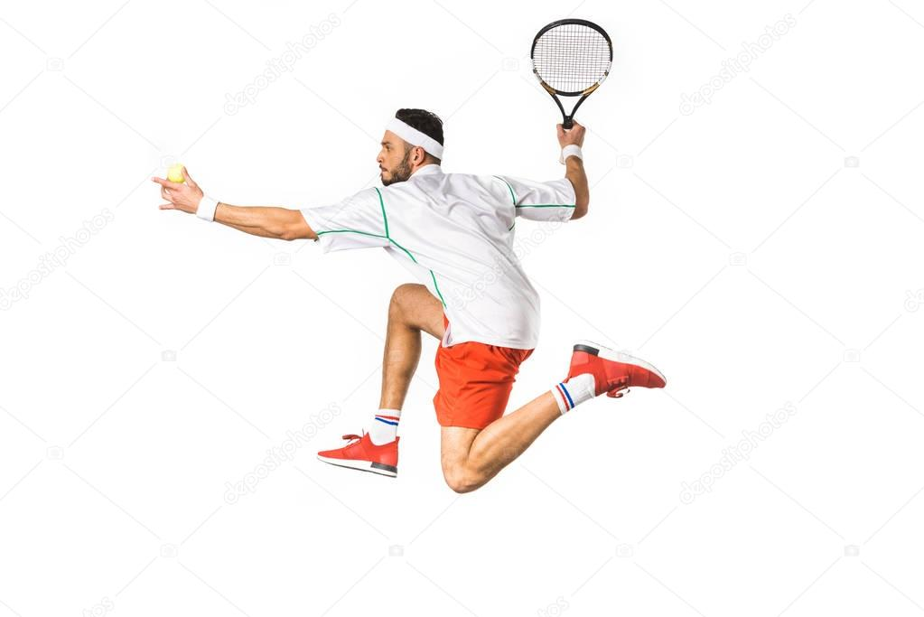 side view of young sportsman with ball and racket playing tennis isolated on white