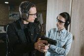 mužské instruktor popisující zbraň pro klientku v střelnice