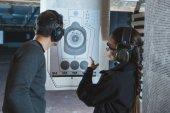 střílení instruktor směřující na použité cíl v střelnice