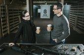 Lächelnder Kunde und Schießlehrer trinken Kaffee im Schießstand