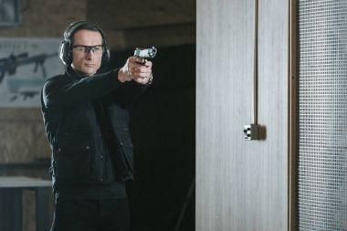 handsome man aiming gun at target in shooting range