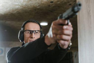 man aiming gun at target in shooting range