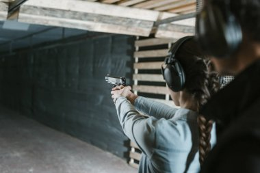 rear view of girl shooting with gun in shooting gallery