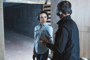 female customer talking with male instructor in shooting range